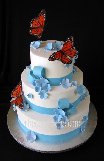 Buttercream cake with sugar flowers, ribbons and bows. Butterflies purchased by client.