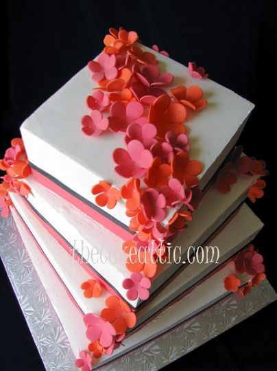 Square buttercream cake with pink and orange sugar flowers and ribbons.