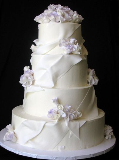 Buttercream cake with fondant drapes and white sugar roses and hydrangeas edged in lavender.