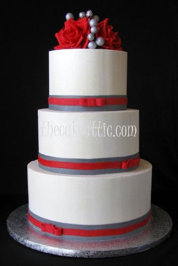 Buttercream cake with red sugar roses, edible silver glitter balls and sugar ribbons and bows.