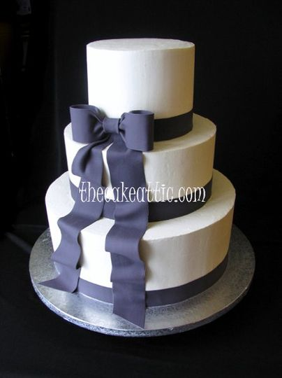 Simple buttercream cake with sugar ribbon and bow in the deep navy used in wedding decorations.