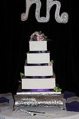 Four tiered wedding cake.   Buttercream icing with satin ribbon border.  Handmade gumpaste flowers...