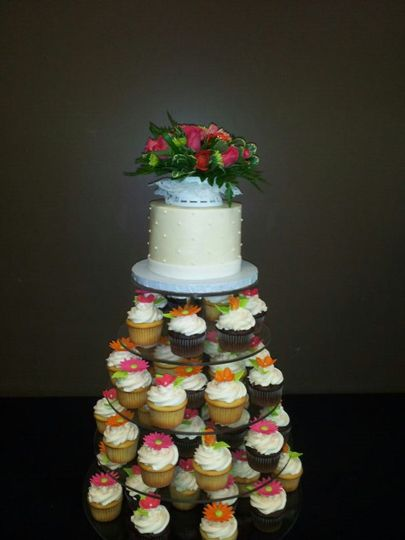 Cupcake tower with small cake with real flowers.  Edible handmade flowers on the cupcakes for...