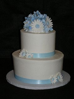 Two tiered wedding cake with buttercream icing.  Handmade gumpaste daisy flowers as cake topper and...