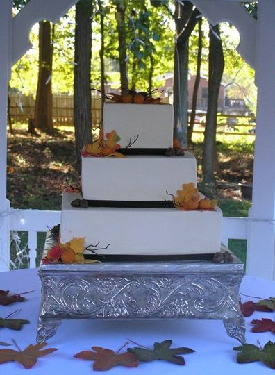 Fall theme three tier square wedding cake with buttercream icing.  Fall decorations of pumpkins,...