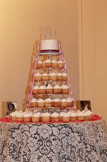 """Cupcake tower with 6"""" cake with silver initials as the cake topper.  Buttercream icing on cake and..."""