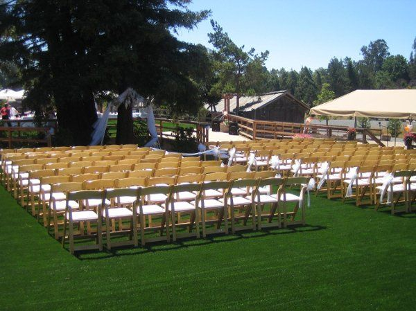 Natural wood folding chairs are lined up viewing the ceremony platform placed under 3 200' tall...
