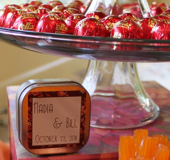 Customized metal favor containers are coordinated with the theme and colors of the event.