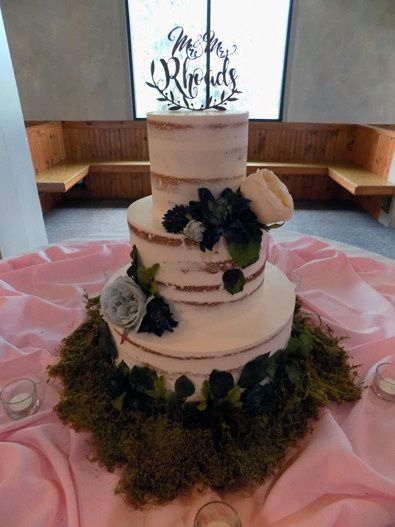 3 Tier semi naked wedding cake decorated with flowers and moss
