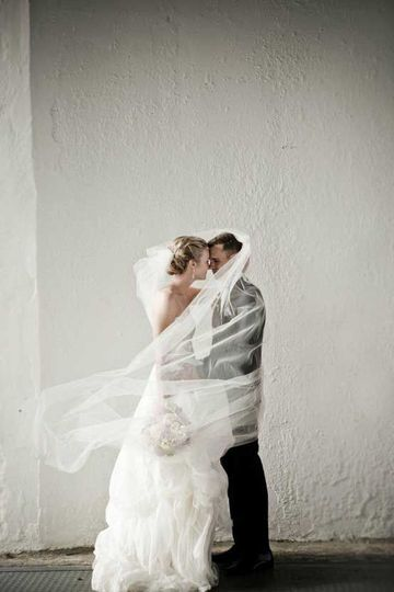 Bride and groom wrapped in the veil