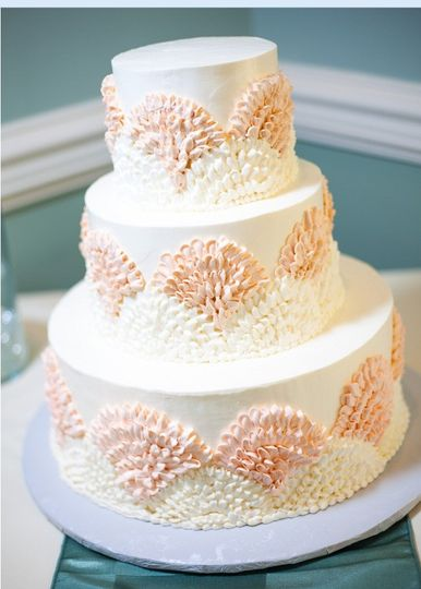 Our classically elegant wedding cake has three beautiful tiers iced in a buttercream fan design,...