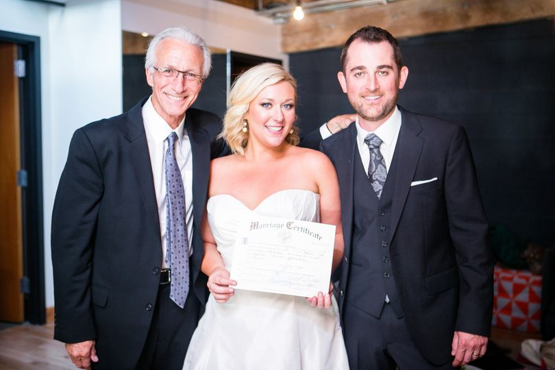Officiant and newlyweds with their certificate
