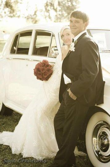 Couple posing beside vintage car