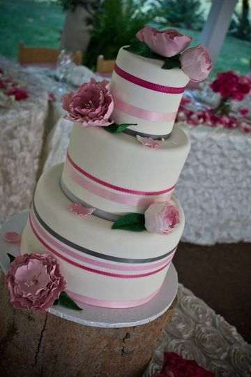 Ribbons in pinks and grey give a little pizzazz to this simple and pretty cake. The sugar flowers...