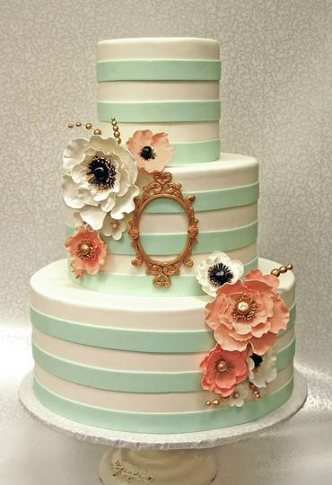 Gorgeous hand-made sugar flowers and an elegant gold frame create a look that feels modern with a...