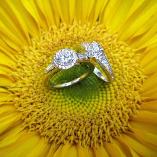A duo of traditional diamond engagement rings set in white gold.
