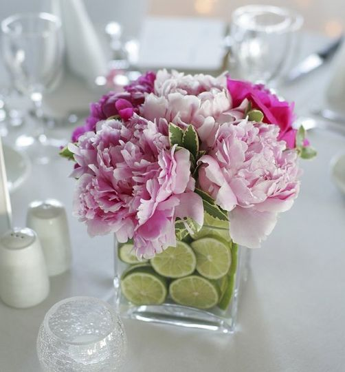 A lush peony arrangement accented with limes in a simply modern cube vase.