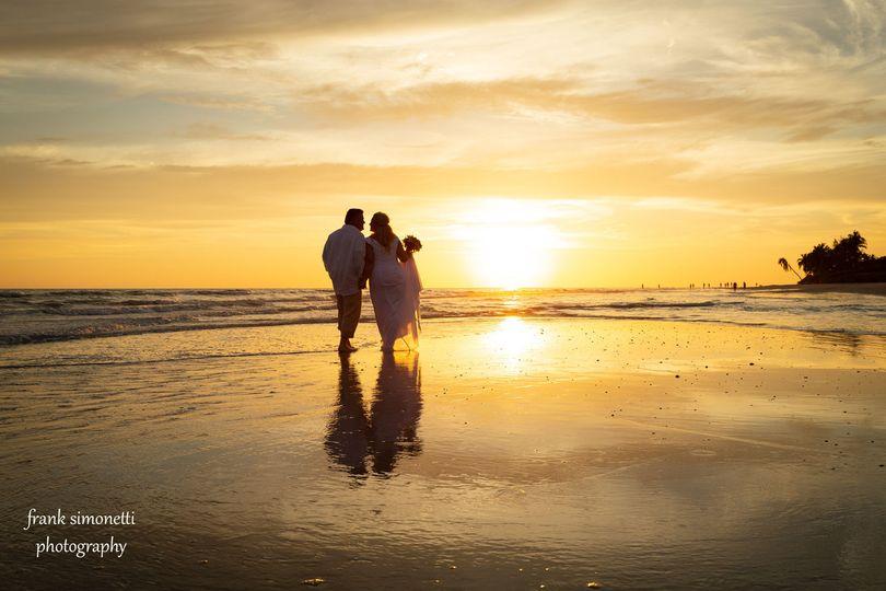 Wedding couple walk into sunset on Sanibel Island