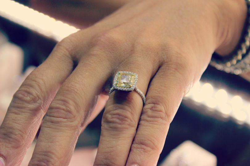 Glittering yellow diamond surrounded by white diamond setting