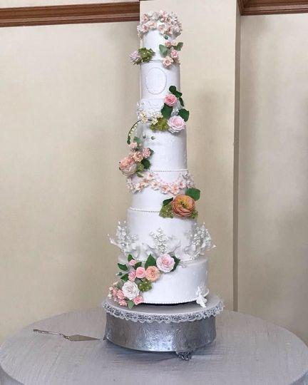 Sugar flowers cascade on a tall beautiful wedding cake