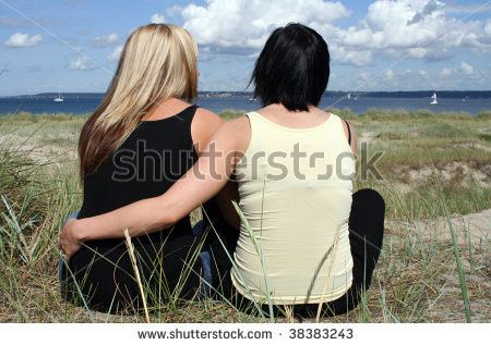 stock photo two young women sitting at the beach h