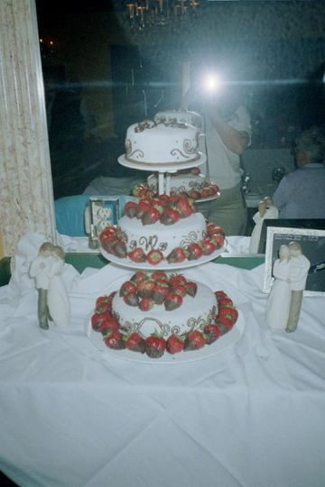 Scrolls and Monograms adorn the sides of this cake and topped with chocolate dipped strawberries