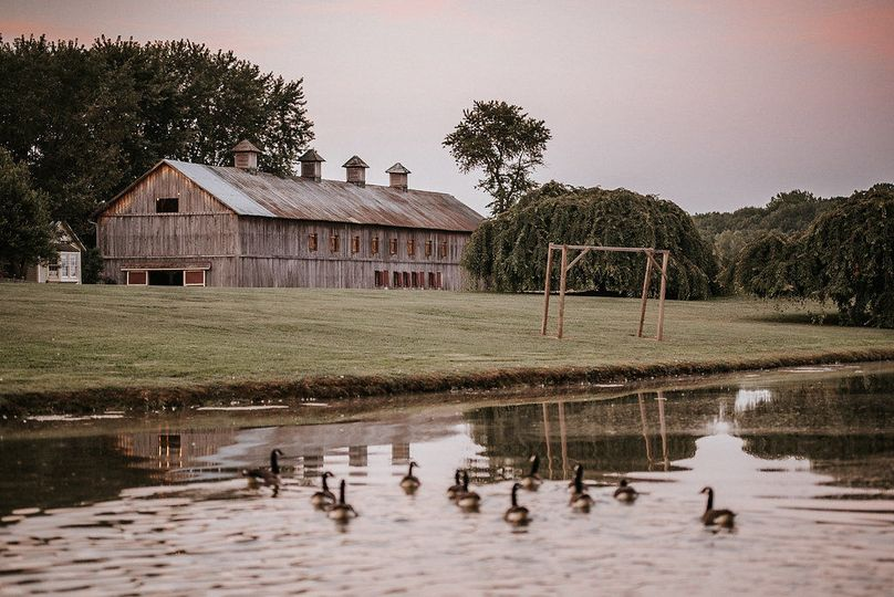 The grass lawn with the pond backdrop is the perfect ceremony site--the Poplar Barn provides an...