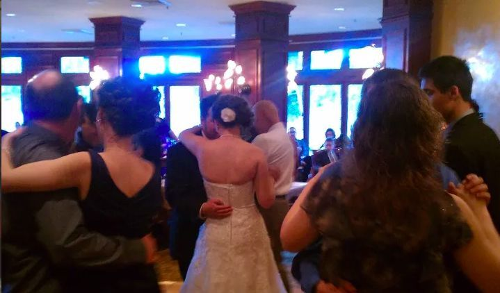 Guests and newlyweds slow dancing