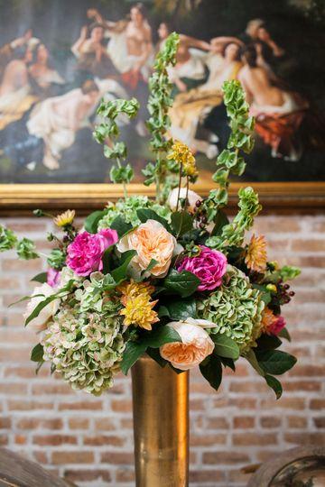 "Table arrangement atop of a narrow, gold ""bullet"" style vase"