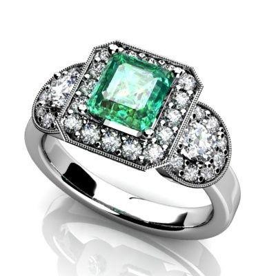 Custom three stone emerald engagement ring. Diamond halos and half moon cut diamonds on each side....
