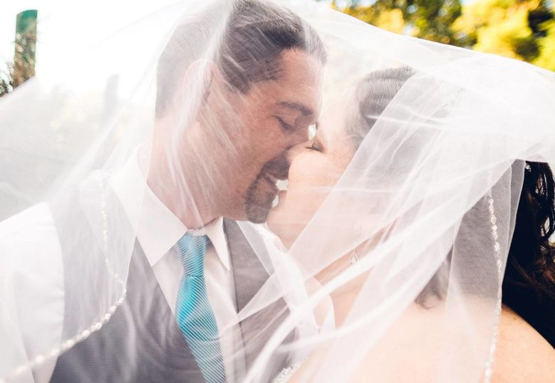 Kiss underneath bride's veil