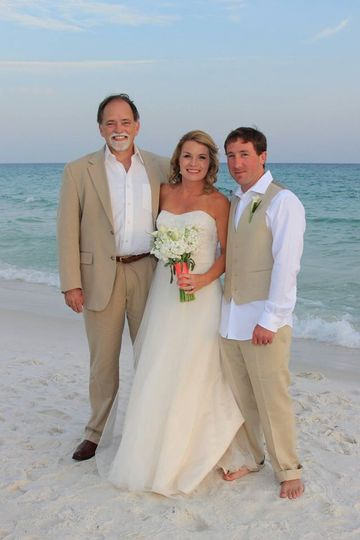 Officiant with the newlyweds at the beach