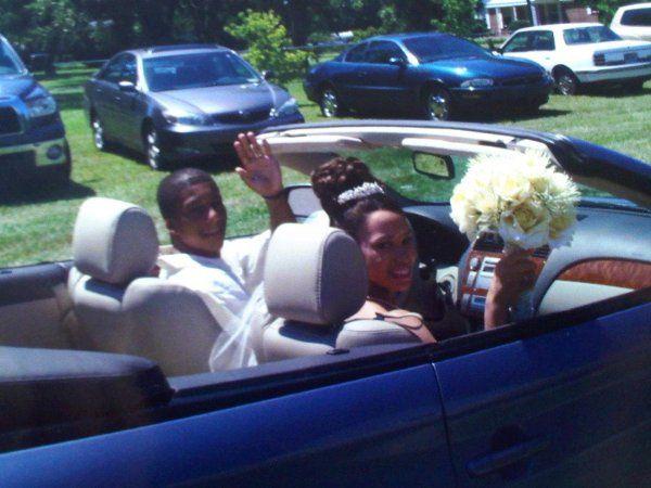 The couple riding their bridal car
