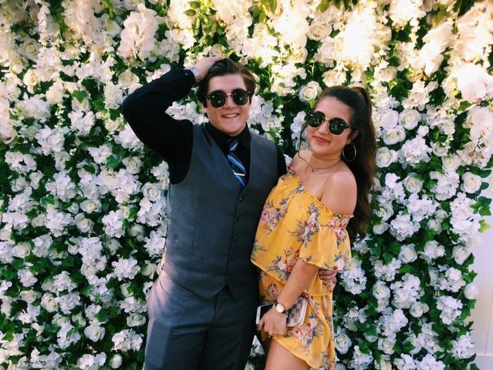 Couple pose by the flower wall