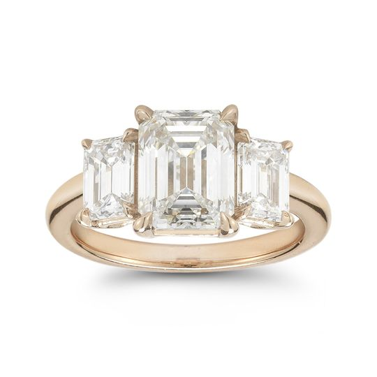 This three stone emerald cut diamond engagement ring features a 2.20 carat center diamond flanked by...