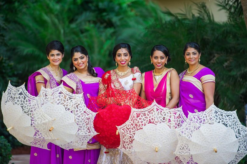 Bride and bridesmaids with ujmbrellas