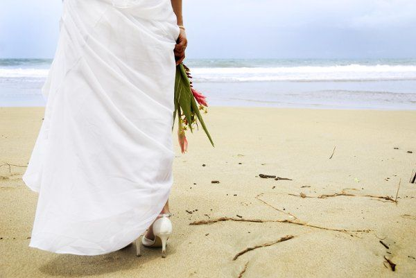A bride holds her tropical bouquet on the white beaches of Costa Rica just before walking down her...
