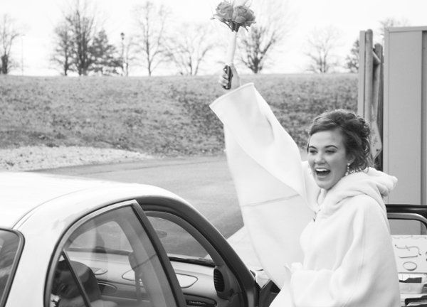 A bride throws her hand up in a victorious goodbye as she climbs in the car to drive off into the...