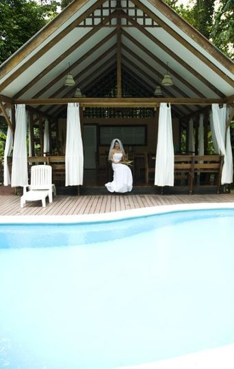 A bride sits by the pool at her lodge before her Costa Rica wedding.