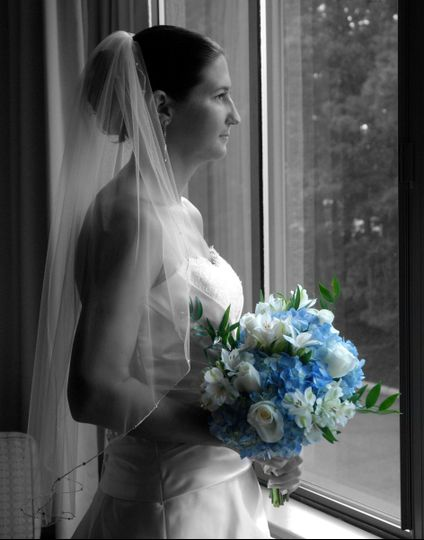 Bride looking out window in black and white with spot color of blue flowers.