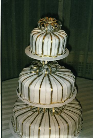 Three tier fondant decorated with gold and silver ribbons and pearls