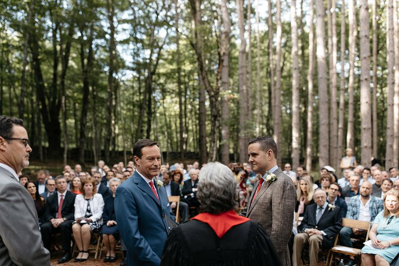 Two grooms getting married in the pine grove at The Roxbury Barn & Estate. Photo by Jean-Laurent...