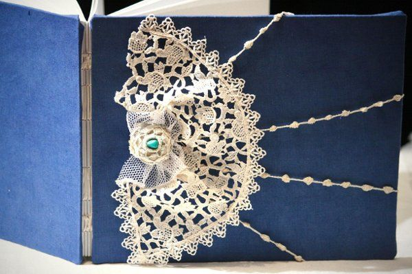 The book wrapped in peacock blue silk and the lace is handmade bobbin lace, pre-1930s is ivory....
