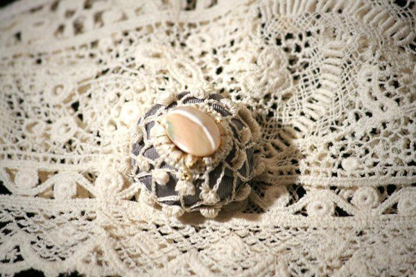 This elegant pin-less brooch is handmade wrapped in Platinum silk and embellished with a crochet...