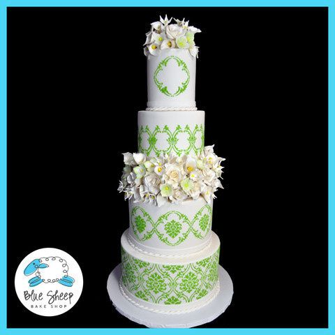 Four tiered white and green lace and floral wedding cake.