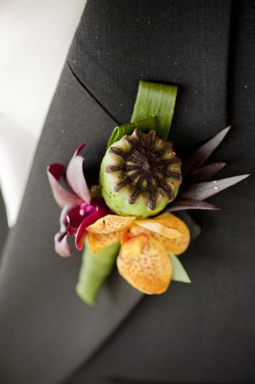 Poppy pod and orchids in a bright, tropical boutonniere.