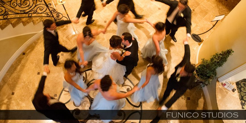 Dancing newlyweds with bridesmaids and groomsmen