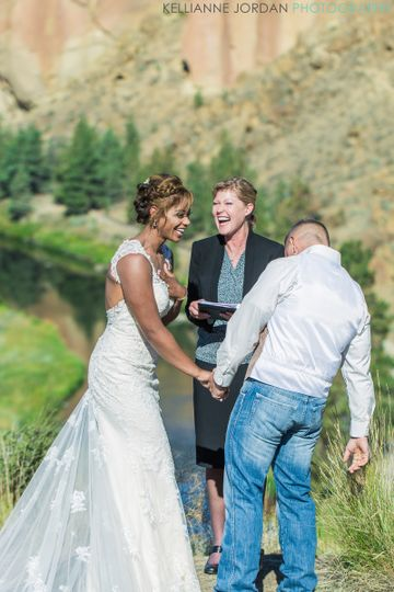 Officiant and couple laughing
