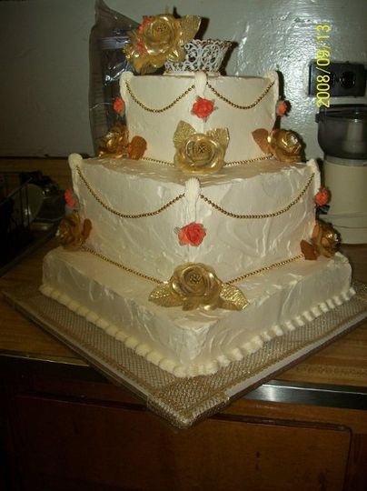 Gold and burnt orange silk flowers adorn this butter cake covered with real butter cream icing! Gold...