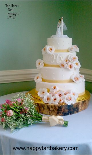 fondant wedding cake with monogram and white roses with gold and pink centers